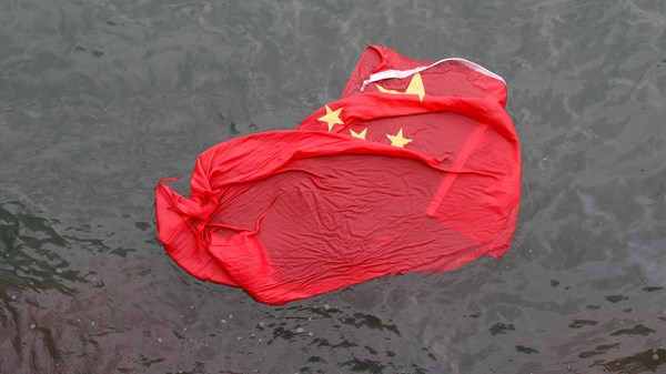 Protesters throw the Chinese flag into the streets